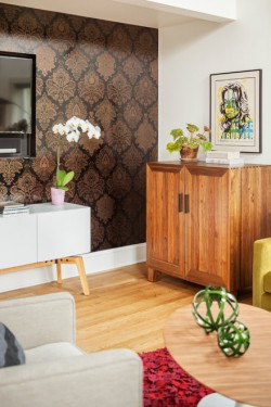 corner of the living area showcases a Fruits of Design wallpaper that's a modern take on traditional damask
