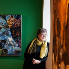 Curator and art historian Susan Danly stands in front of Dahlov Ipcar's Blue Savanna, 1978, currently on display at the Portland Museum of Art.