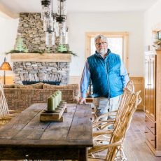 Scott Stone stands in the open living area of the Lake House, one of six model homes on show at the Schiavi headquarters in Oxford. An industrial-style fixture fitted with Edison bulbs paired with a salvaged wood table and chairs crafted from vines creates a modern-woodsy vibe.