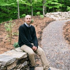 Keith Stone rests on a fieldstone sitting wall equipped with landscape lighting he recently completed on Peabody Pond in Sebago.