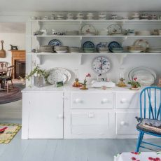 The farmhouse kitchen is largely original and features open shelves stacked with blue-and-white Willow dishware and other china. Through the door, one can see the dining room with its original fireplace and wood surround. An old wooden grain shovel hangs to the left of the mantel.