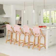 """The airy kitchen has a cooking zone and a clean-up/prep zone that share an eight-foot-long island topped with Danby marble from Morningstar Stone and Tile in Topsham. A full-height backsplash of marble and mirrored tiles reflects the water. Banks allowed for pops of homeowner Kim Nemser's favorite color in the pendant lights, stove knobs, and rattan French bistro stools—one of the designer's go-to chairs because they're """"scrubbable, lightweight, and don't scratch the floor."""""""