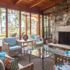 The screened porch in this Littlejohn Island home contains furnishings from Simply Home in Falmouth, ME, bark lanterns from Dwellings and antique oil paintings from Pillars