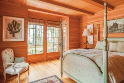 A guest room in the Littlejohn Island home features a bed with slender posts and a 1960s faux bois chair from pillars