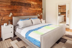 The master bedroom features a reclaimed wood wall which serves as a divider between the bedroom and closet