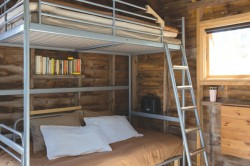 The bunkhouse features a bunkbed made by combining a loft bed and a day bed