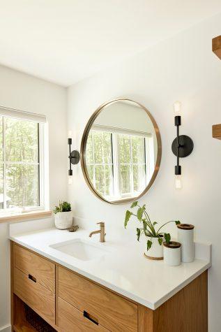The striking circular bathroom mirror completes the