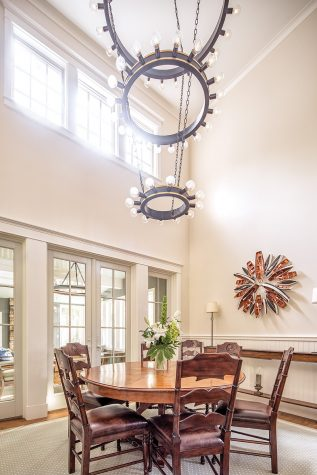 Designer Louise Hurlbutt commissioned a three-tiered chandelier for the vaulted dining room space, which hangs over an expandable reproduction table first patented by English furniture maker Theodore Alexander Robert Jupe in 1843.