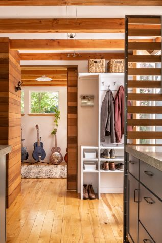 In tight quarters, compartmentalizing spaces without resorting to solid walls that would chop the space up was important. A wood-slat screen and mudroom-style cubbies create a sense of entry, partially separating the area from the kitchen.
