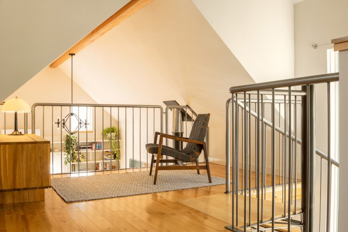 The stair culminates between a sitting room overlooking the living area and the bedroom.