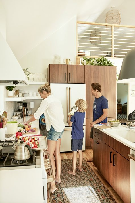 The family gather in the kitchen to prepare food.