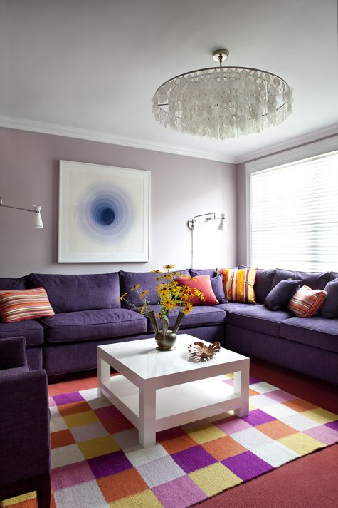 A custom sofa in a lively shade of plum fills the corner of this interior living room design by Glenn Gissler.