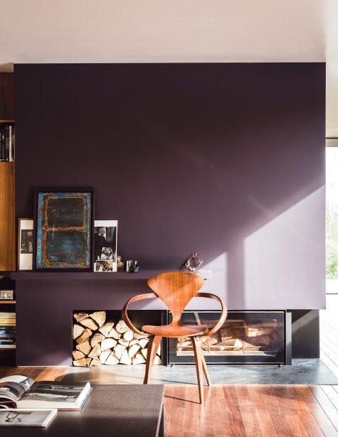 "Norman Cherner's iconic ""Pretzel"" armchair sits in a plum interior design"
